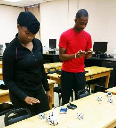 Raquel Boulware, Donald Davis test robots while conducting research at Claflin in human computer interaction