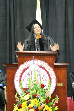 Margarita Anderson Speaking at Podium in Cap and Gown